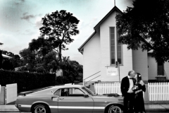 black and white photo of church, the couple and mustang with the sky in colour
