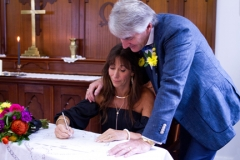signing the paper work at their wedding at Tweed River Chapel