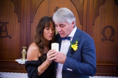 in Tweed Valley Chapel, bride and groom hold and blow out a candle
