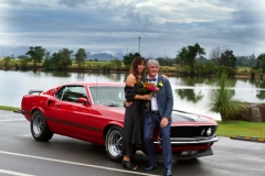 bride and groom posing in front of the mustang and the Tweed River at Tumbulgum