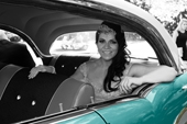 Bride in car, black and white photo with car in brilliant colour
