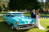 Bride and Groom with the car