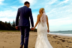 Bride and groom walking away on the beach, blue sky with great cloud formations