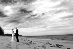 black and white bride and groom standing on the beach