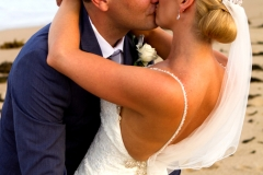 Groom leaning over bride for a kiss