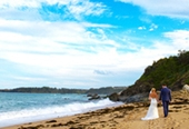 Kristy and Gabe, walking on the beach with vivid sky
