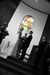 At the alter, black and white photo with a colour stained glass window