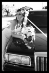 Bride leaning on wedding car