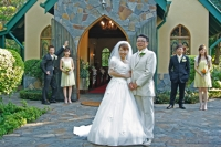 Minako and Shunya with the bridal party in the background in front of the chapel