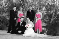 The bridal party in black and white with the stunning pink bridesmaid dressed in colour