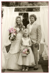 sepia photo of bride, groom and their daughter