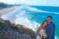 Panoramic shot of the couple on rocks with all the beach in background