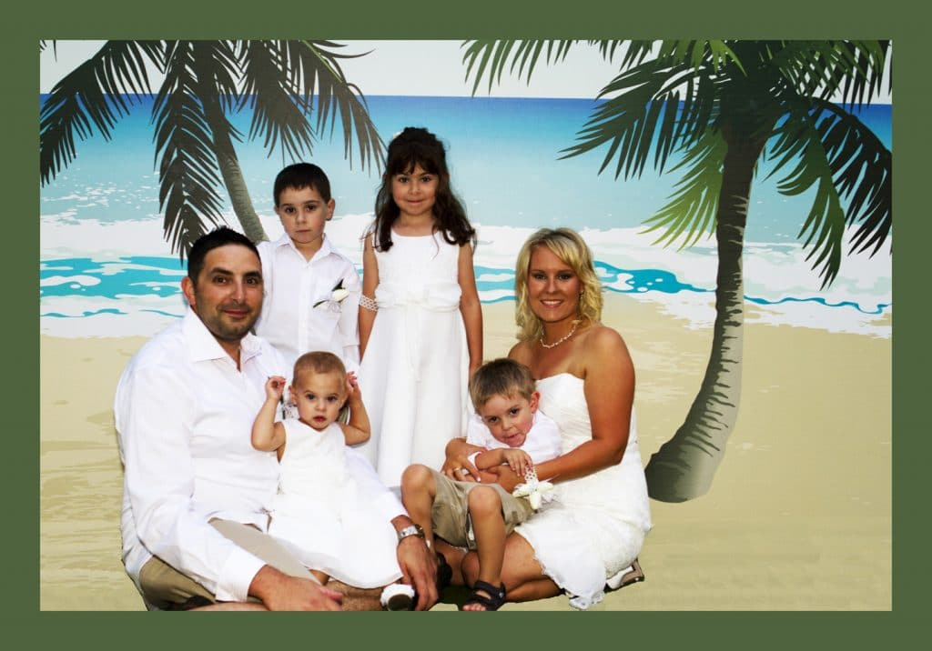 Young family holidaying on the Gold Coast, family portrait in front of beach and palm tree painted back drop