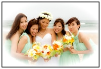bride with two brides maids on either side, dressed in mint dresses and holding flowers