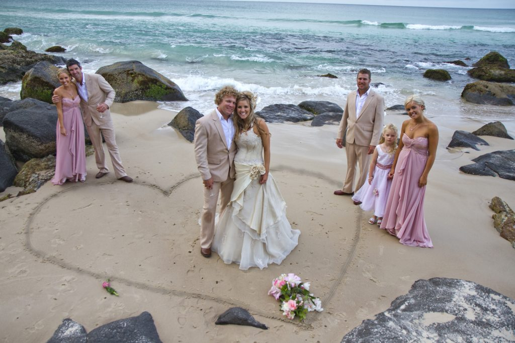 bride and groom in a heart drawn in sand on beach with bridal party around it