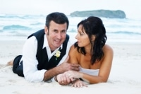 bride and groom lying on the beach at Fingal