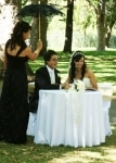 Couple signing register whilst bridesmaid holds sun umbrella over the couple