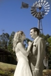 bride and groom looking at each other by a windmill
