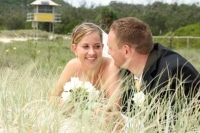 couple laying in the sand dunes on their wedding day at Palm Beach