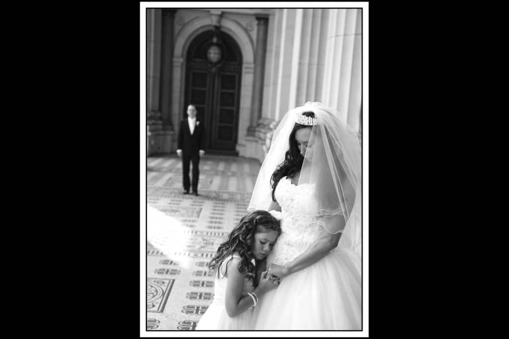 groom in background, bride and grooms daughter bonding in foreground, black and white photo
